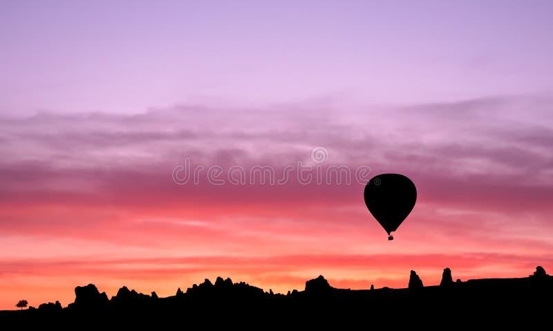 Heißluftballonschattenbild in den Bergen bei Sonnenaufgang, Goreme, Capp stockbild