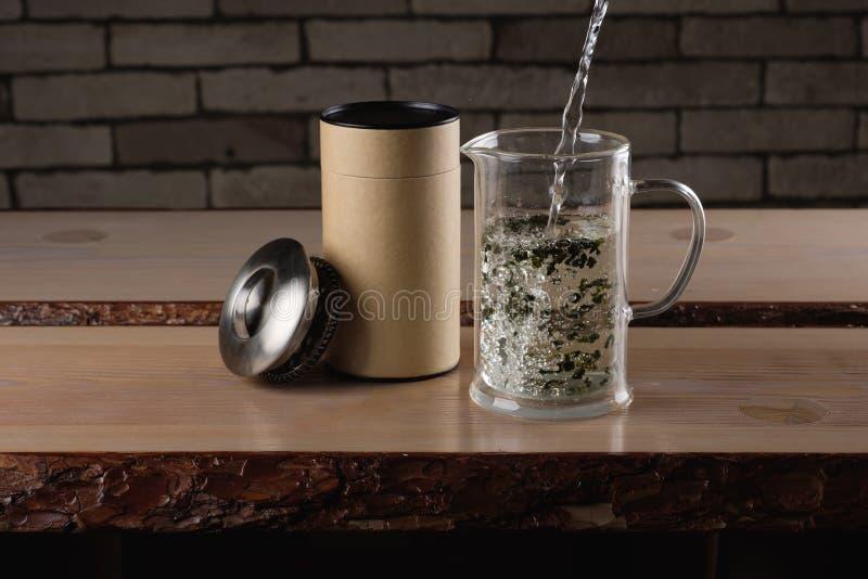 Heißwasser, das zu einer Glasteekanne mit grünem Tee gießt stockbilder