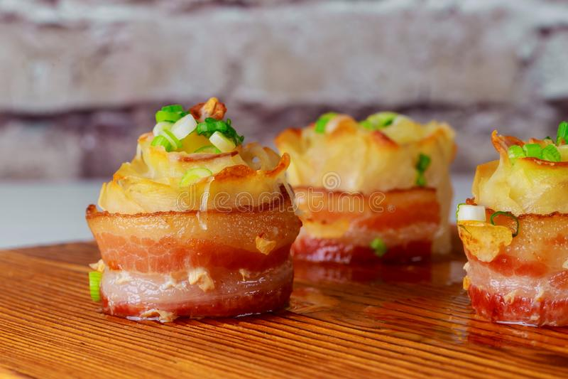 Heiße Ofenkartoffeln mit Käse, Speck und Zwiebel sclose-up auf hölzernem Hintergrund stockbild