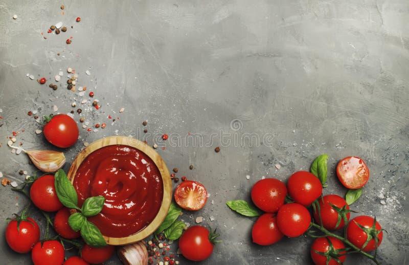 Heiße Tomaten-Ketschup-Soße mit Knoblauch, Gewürzen und grünem Basilikum mit Kirschtomaten in der hölzernen Schüssel auf grauem K lizenzfreies stockfoto