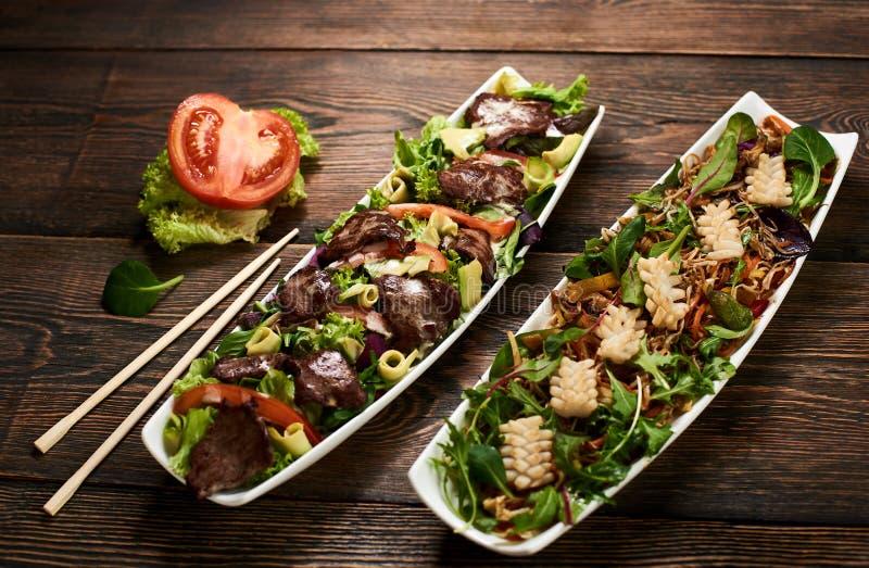 Heißer Salat mit Kalmar, Sojabohnensprösslinge, Rindfleisch, Avocado, rucola auf Rezept der asiatischen Küche in der weißen Platt stockfotos