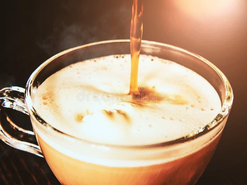 Hei?er Kaffee wird aus dem t?rkischer Kaffee makere in eine transparente Schale Eiscreme gegossen stockbilder
