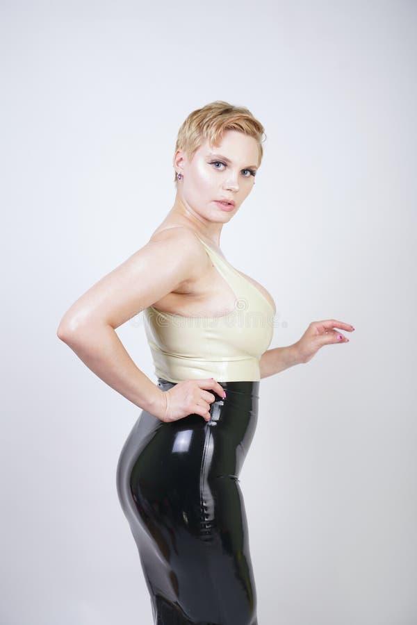 Hei?es blondes M?dchen des kurzen Haares mit tragendem Latexkleid des curvy K?rpers auf wei?em Studiohintergrund lizenzfreie stockfotografie