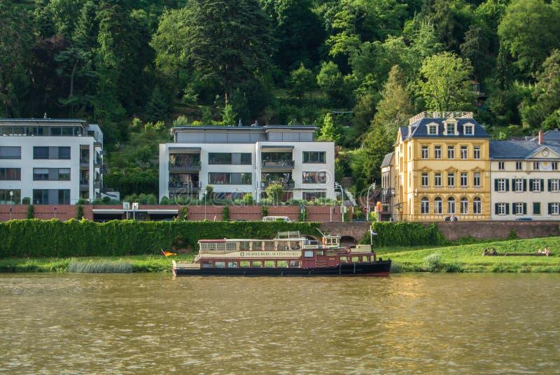 HEIDELBERG, GERMANIA - 4 GIUGNO 2017: Un ambankment del fiume Neckar con le case variopinte e una nave immagini stock libere da diritti