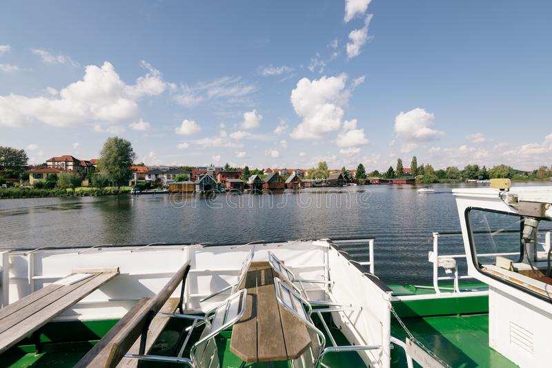 Heidensee lake; in Schwerin; Germany. Schwerin; Germany - Sept 10; 2017: Touristboat passing by a row of lake houses on the Heidensee lake; in Schwerin; Germany stock images
