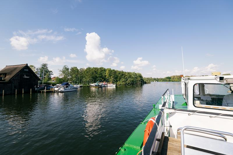 Heidensee lake; in Schwerin; Germany. Schwerin, Germany - Sept 10, 2017: A tourist boat passing by a boat house on Heidensee lake in Schwerin, Germany royalty free stock image