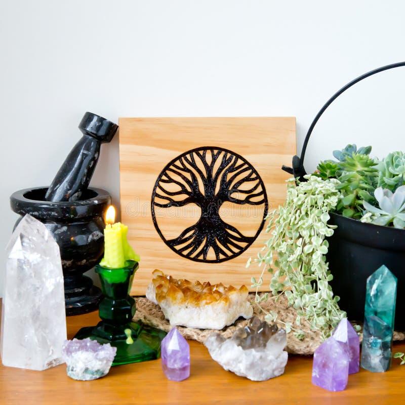 Heidnischer Altar-Raum mit Baum der hölzernen Fliese, des Mörsers und der Stampfe, der Kerzen und der Kristalle des Lebens lizenzfreies stockbild