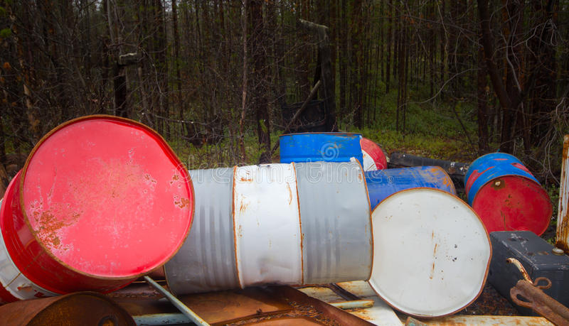 Height of mismanagement and irresponsibility. Colorful empty barrel of fuel left in forest. Frozen limit (mismanagement and irresponsibility). Colorful empty stock photo