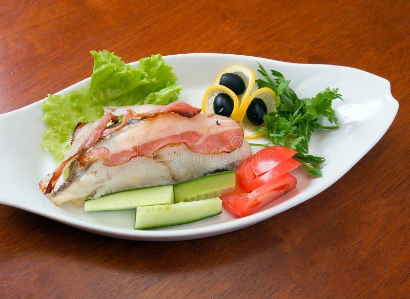 Heilbot die met groenten en bacon wordt voorbereid stock foto's