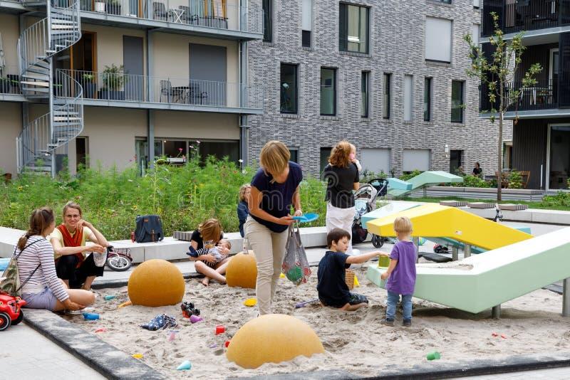 Heilbronn, Alemanha - 12 de agosto de 2019 Mães com crianças pequenas brincam na caixa de areia do parquinho entre prédios modern imagem de stock royalty free