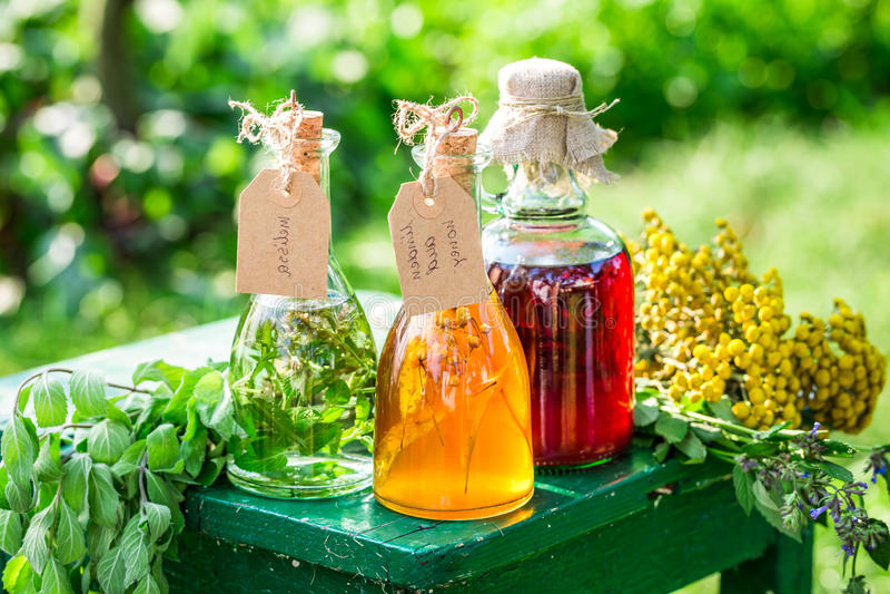 Heilende Kräuter in den Flaschen als selbst gemachter Heilung im Garten stockbilder