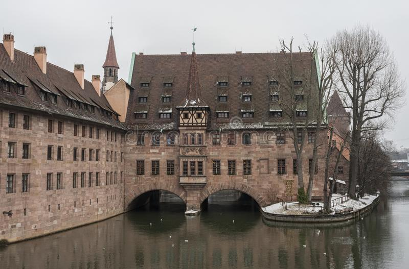 Heilig-Geist-Spital Hospice of the Holy Spirit in Old Town Nuremberg. View from the Museum Bridge on the on the River Pegnitz royalty free stock photo