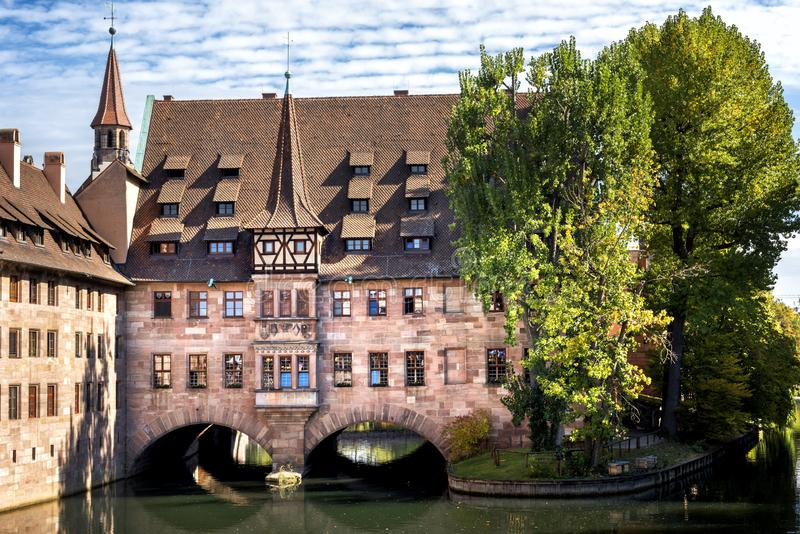 Nuremberg, Heilig-Geist-Spital which is reflected in the waters of the Pegnitz river. Franconia, Germany royalty free stock image