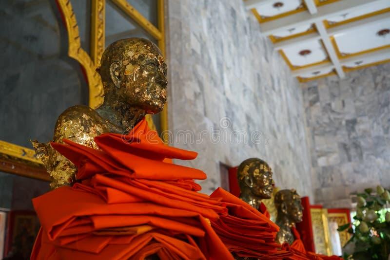 Heilige heilige alte sitzende Statue mit goldenem Blatt des verletzbaren Mönchbildes, Luang Pho Chaem, mit dem gelben Roben-Angeb stockfotos