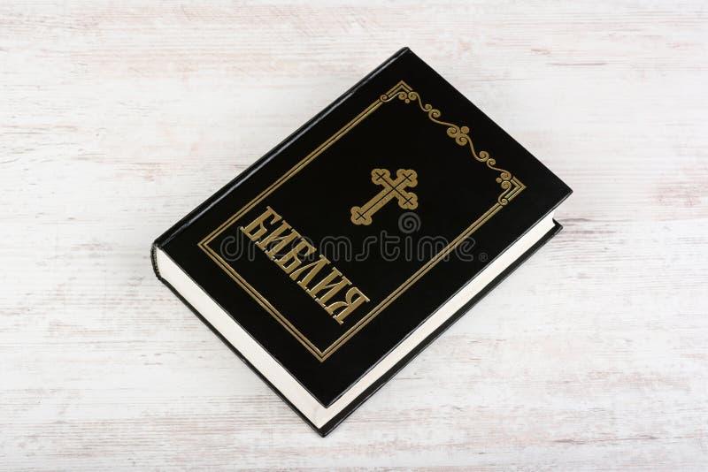 Heilige Bibel auf weißem hölzernem Hintergrund Religionskonzept und -glaube Kyrillischer Text bedeutet Bibel herein lizenzfreies stockbild