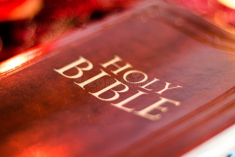 Heilige Bijbel met gedrukte decoratieve leerdekking op lijst met zacht trillend kaarslicht royalty-vrije stock foto's