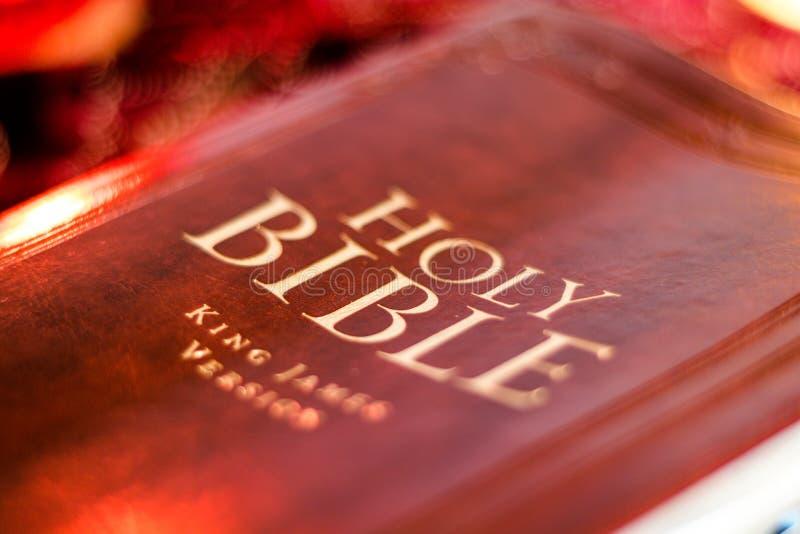 Heilige Bijbel met gedrukte decoratieve leerdekking op lijst met zacht trillend kaarslicht royalty-vrije stock fotografie