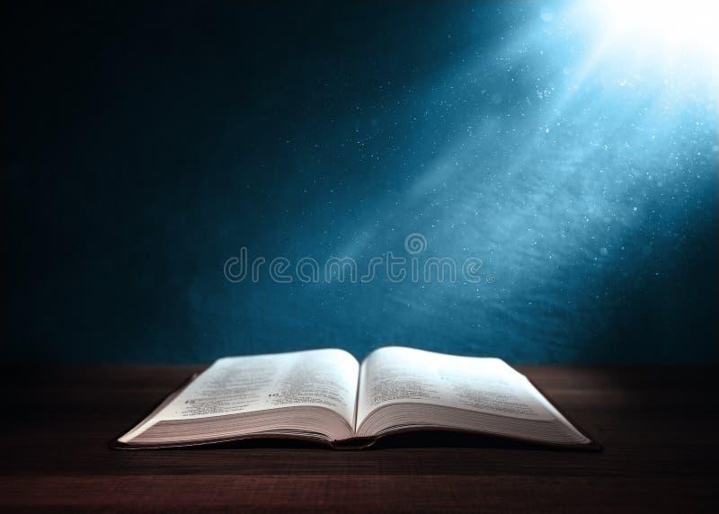 Heilige die Bijbel op een houten lijst wordt verlicht stock afbeelding