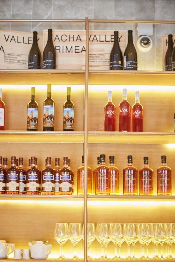 Heilige-Peterburg, Rusland: 24 augustus 2018: Wijnflessen op houten plank in wijnopslag stock fotografie