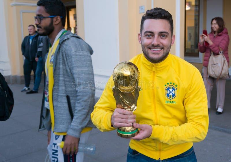 HEILIGE-PETERSBURG, RUSLAND - JUNI 22, 2018: De knappe Braziliaanse voetbalfan glimlacht en houdt een kop royalty-vrije stock afbeeldingen