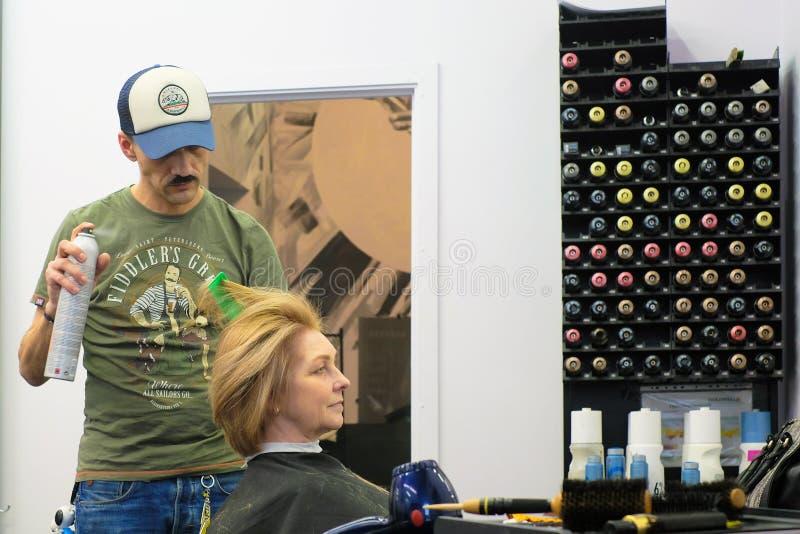 Heilige-Petersburg Rusland 11 09 2018 maakt de meester van haar het stileren cliënthaar royalty-vrije stock afbeelding
