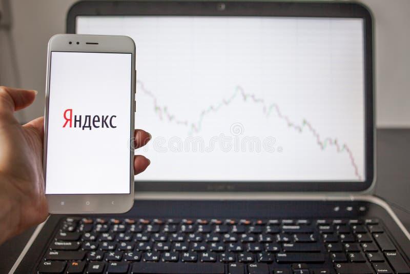 HEILIGE PETERSBURG, RUSLAND - MEI 14, 2019: embleem van het Russische IT bedrijf Yandex op de achtergrond van voorraadgrafieken royalty-vrije stock foto's