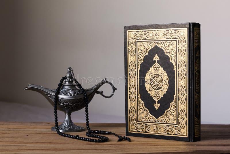 Heiliger Quran auf dem wodden Hintergrund mit einer Rosenbeet- und Ägypten-Wunderlampe - Al Ramadans kareem/Eid fitr Konzept lizenzfreie stockfotos