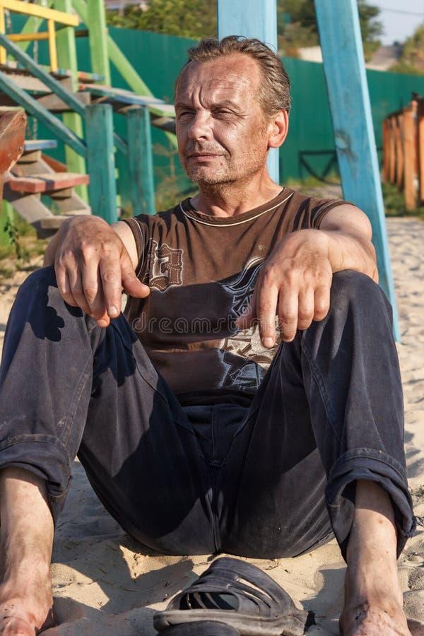 Heimatloser Mann Arme Leute im Kind-` s Spielplatz am sunse lizenzfreie stockbilder
