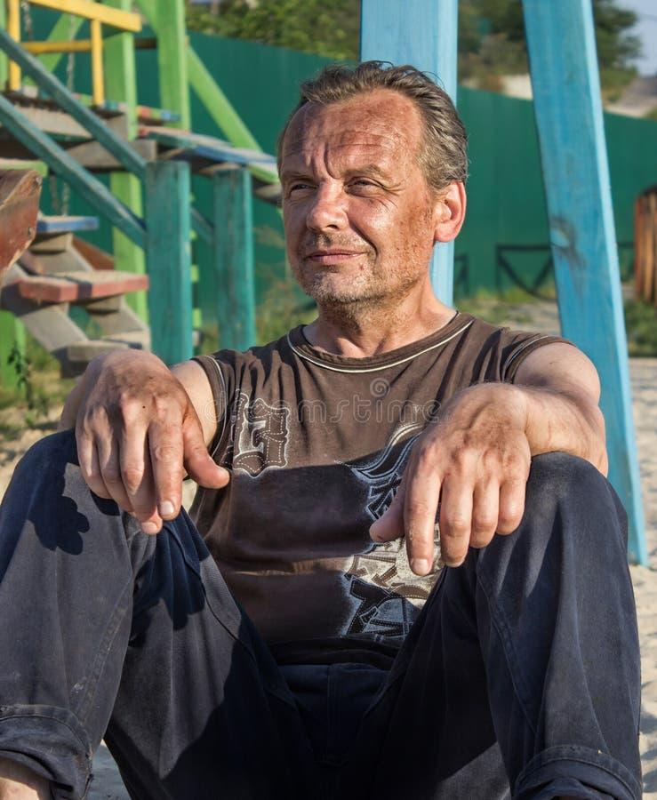 Heimatloser Mann Arme Leute im Kind-` s Spielplatz am sunse stockfotografie