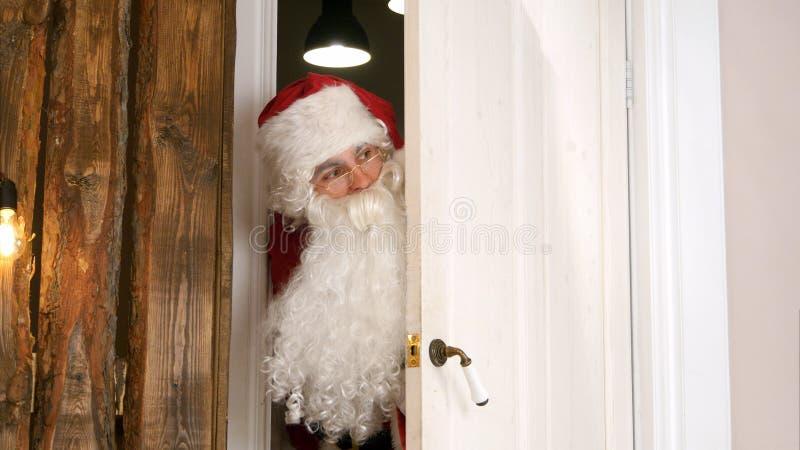 Heimelijk nemen Santa Claus die in het geheim de woonkamer ingaan stock fotografie