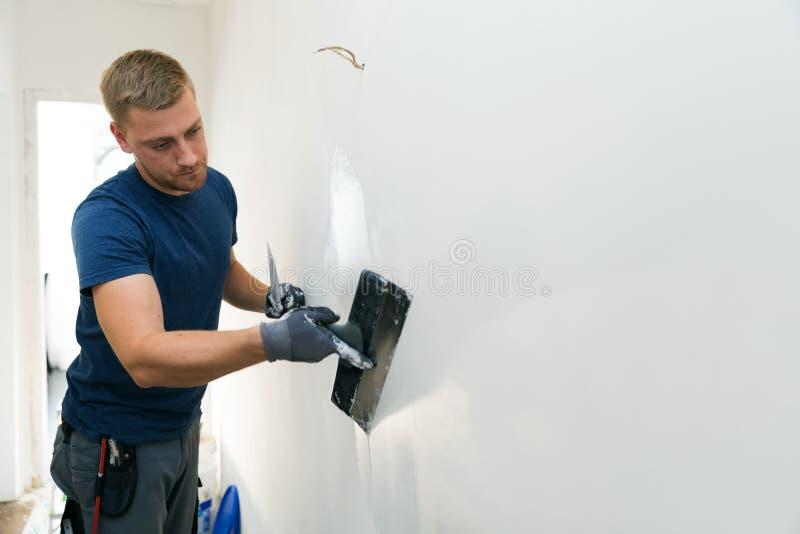 Heimwerken - Bauarbeiter, der Wohnungswände erneuert lizenzfreies stockfoto