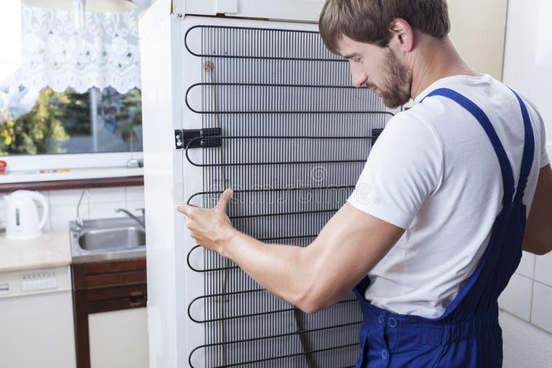 Heimwerker, der den Kühlschrank repariert stockbilder