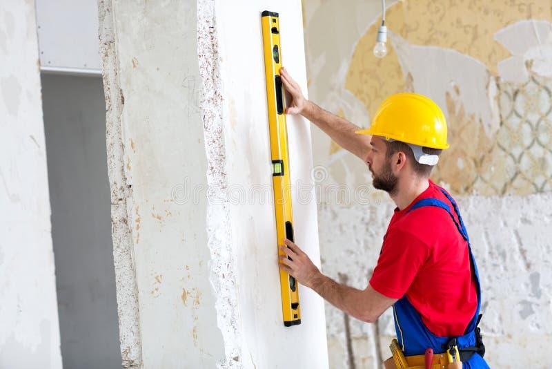 Heimwerker, der die Wasserspiegel und Prüfung hält lizenzfreie stockfotografie