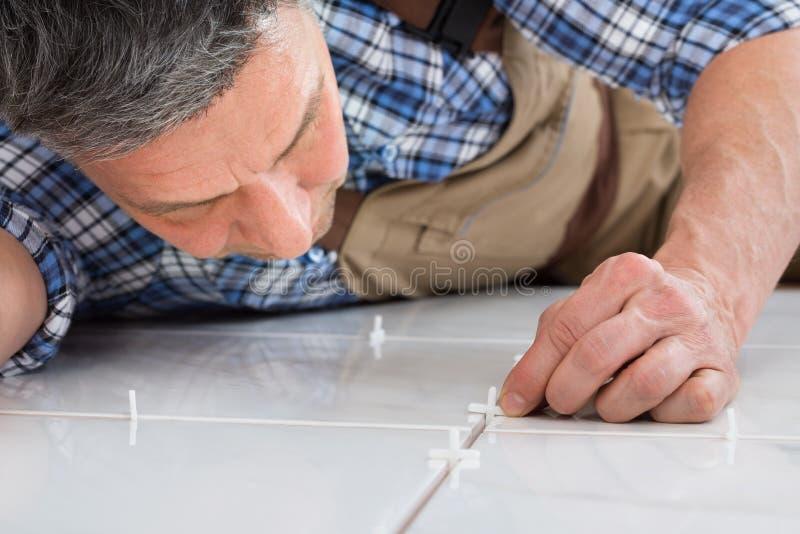 Heimwerker, der Distanzscheiben zwischen Fliesen setzt stockfotos