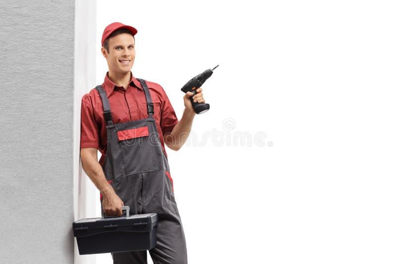 Heimwerker, der eine Bohrgerätmaschine und einen Werkzeugkasten lehnend an der Wand und an der Aufstellung hält stockfoto