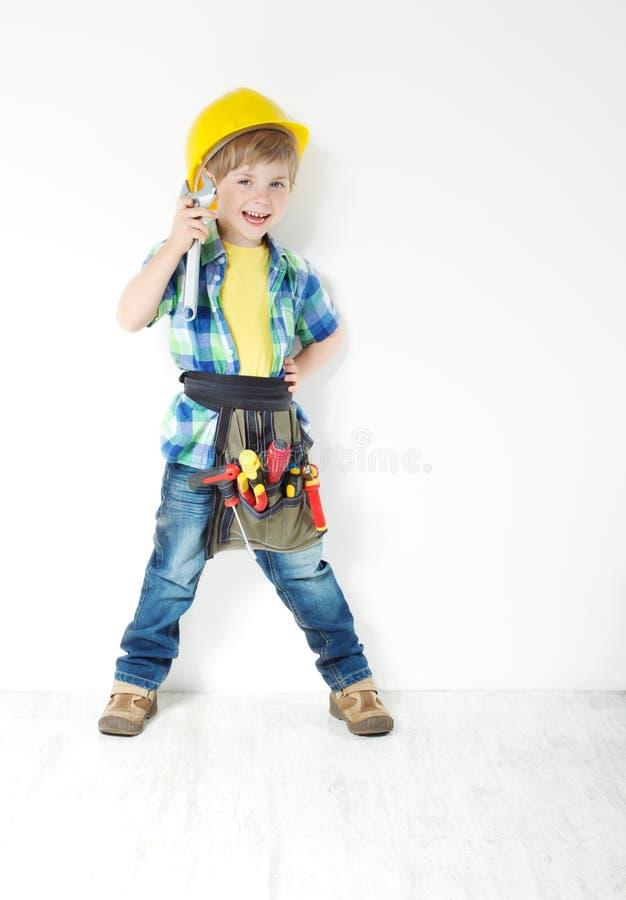 Heimwerker des kleinen Jungen mit Sturzhelm- und Hilfsmittelgurt stockbilder