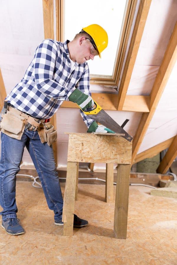 Heimwerker im gelben Schutzhelm mit einem Werkzeuggurt Kopieren Sie Raum Dachbodenerneuerung stockfotos