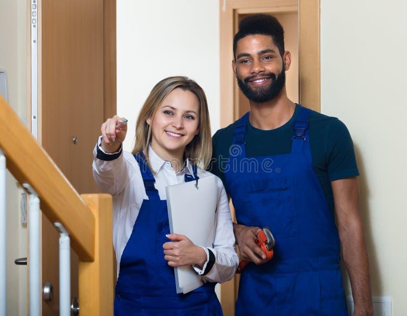 Heimwerker mit Assistenten am Eingang lizenzfreie stockfotos