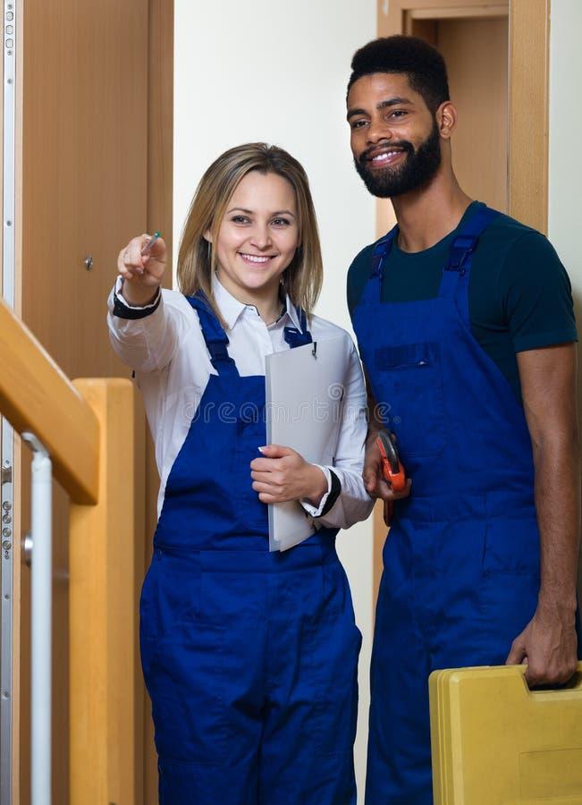 Heimwerker mit Assistenten am Eingang lizenzfreie stockfotografie