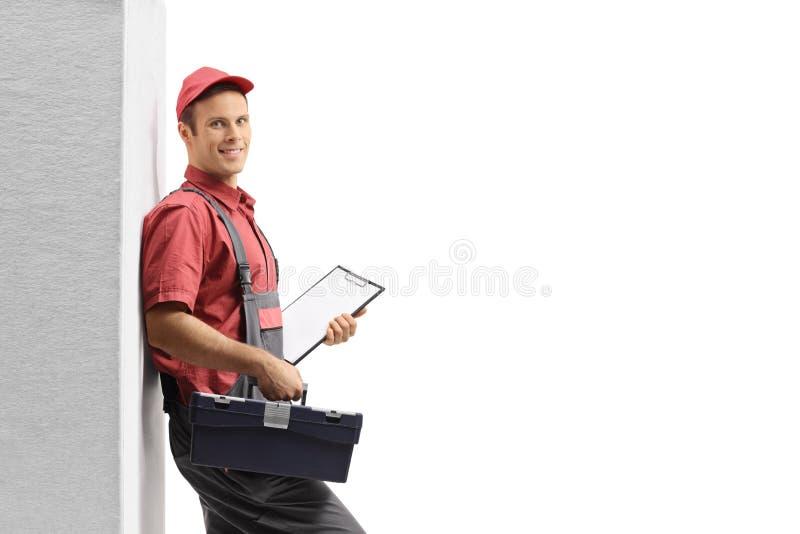 Heimwerker mit einem Klemmbrett und einem Werkzeugkasten, die an der Wand sich lehnen stockfotos
