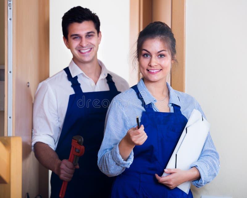 Heimwerker und Assistent in der Uniform lizenzfreies stockfoto