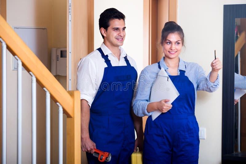 Heimwerker und Assistent in der Uniform lizenzfreie stockfotos