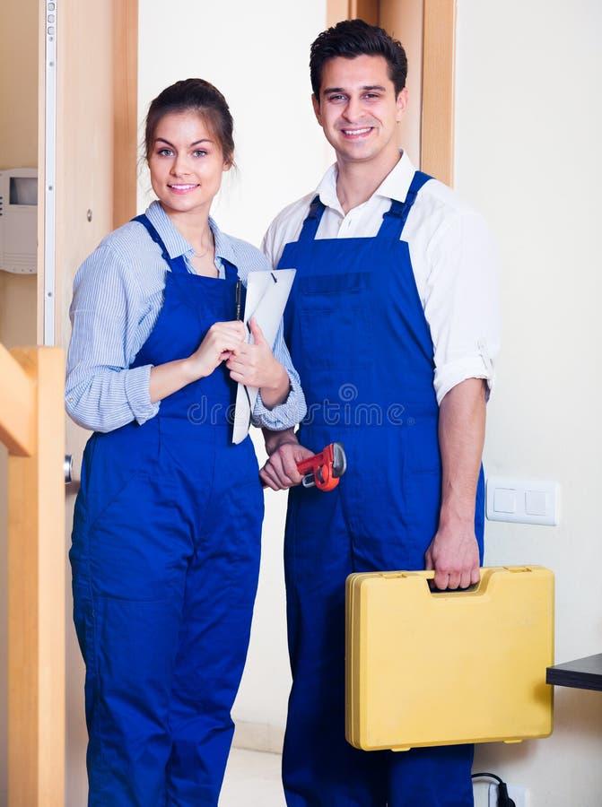 Heimwerker und Assistent in der Uniform stockbild