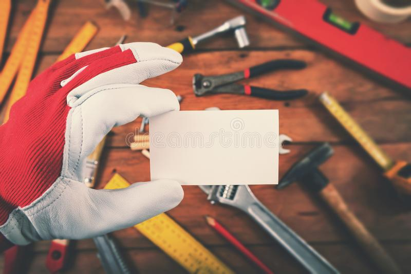 Heimwerker und Hauptreparaturdienstleistungen - Hand, die leere Visitenkarte über den Arbeitswerkzeugen hält stockfotos