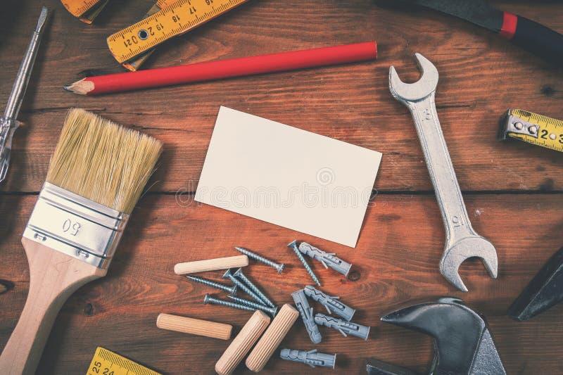 Heimwerkerservice-Hauptreparatur - leere Visitenkarte mit Bauwerkzeugen auf hölzernem Hintergrund stockfotografie