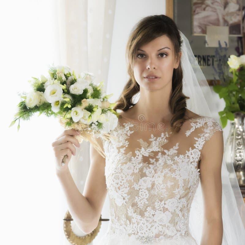Heirat, schöne junge Braut mit Blumenstrauß lizenzfreie stockfotos