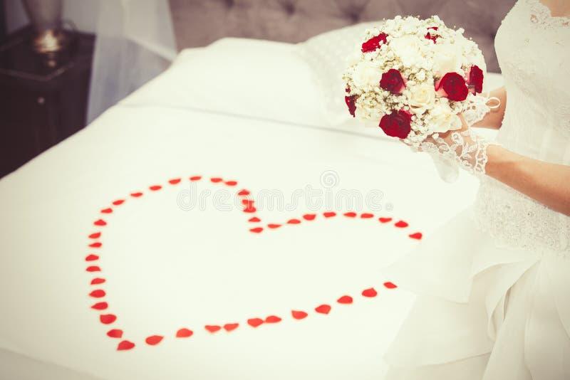 Heiraten Sie, Heirat Braut zu Hause Brautbett Blumenblattherzform lizenzfreies stockbild