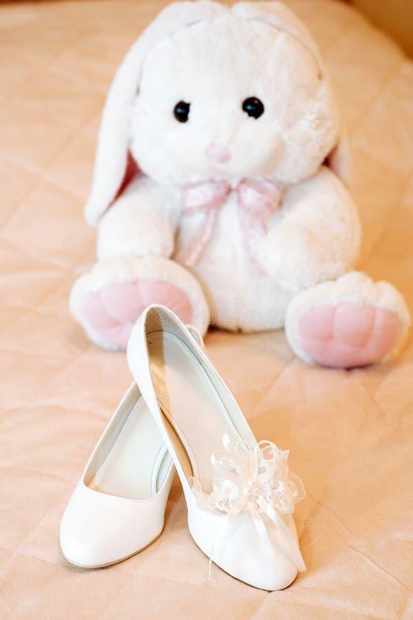 Heiratende Brautschuhe und Plüschspielzeughäschen weiß stockfotografie
