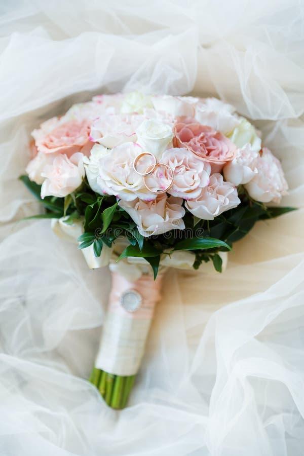 Heiratende goldene Ringe mit rosa Pastellrose stockbild