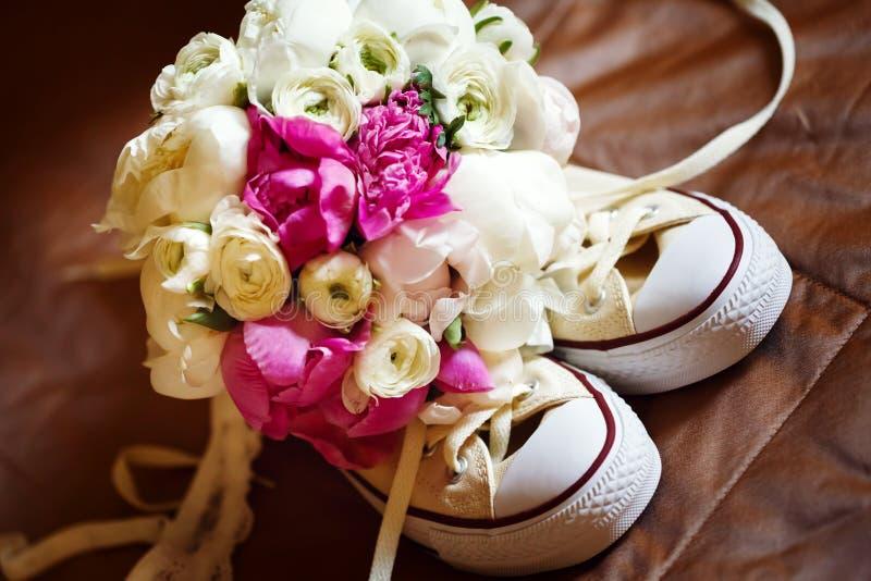 Heiratende rosa Blumen mit Turnschuhen lizenzfreie stockfotografie